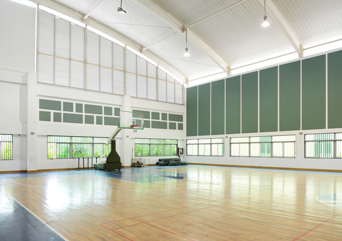 photo of a gymnasium basketball court with 1 Series premade acoustic panel mosaic and 3 Series Sectional acoustic bands on walls (Large)