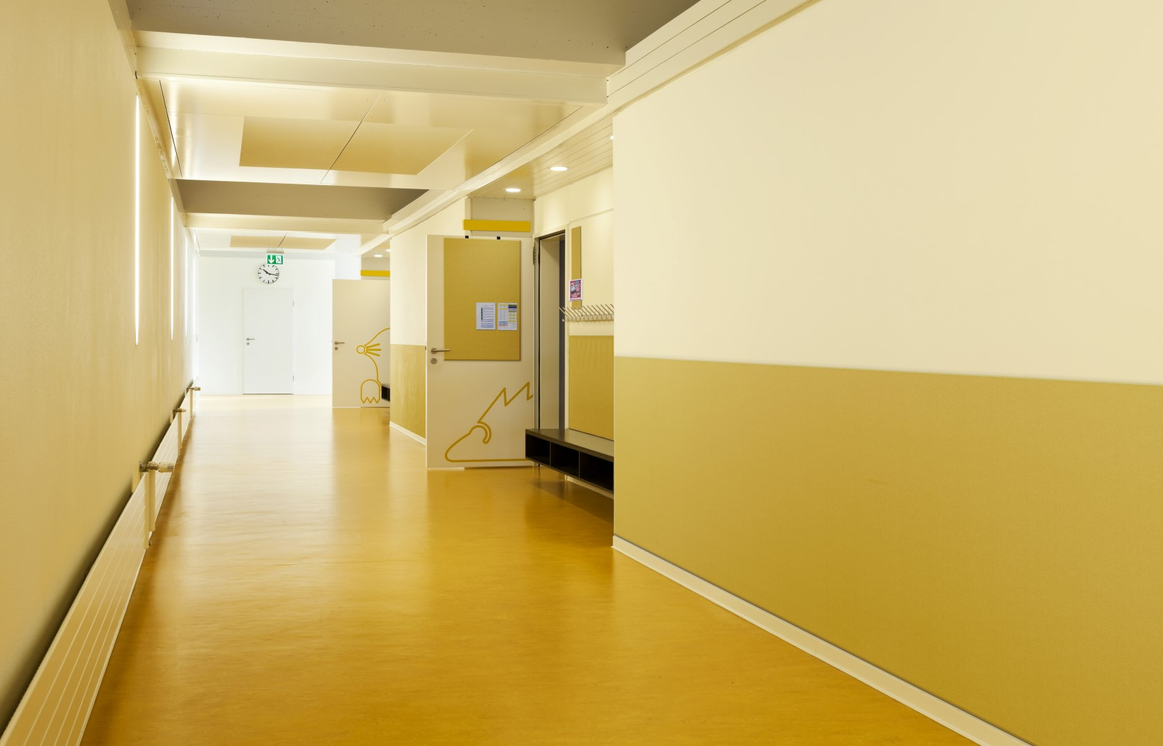photo of a school hallway with fabric covered wainscoting and fabric covered bulletin board panels as tackstrips and doorboards (Large)